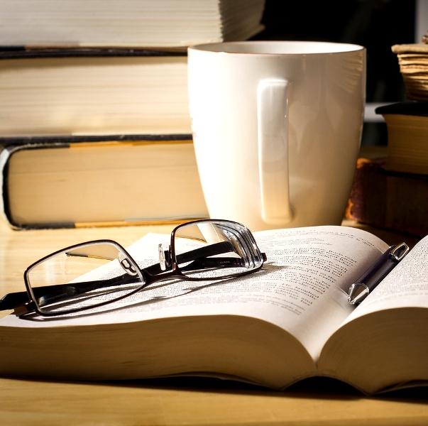Книги, очки, ручка и чашка на столе